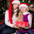 Mother and daughter open gifts near a Christmas tree. — Stock Photo #34350445