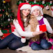 Mother and daughter open gifts near a Christmas tree. — Stock Photo #34350459