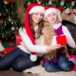 Mother and daughter open gifts near a Christmas tree. — Stock Photo