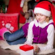 Girl with a gift in a Christmas hat — Stock Photo