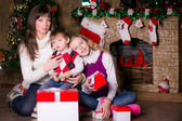 Family near the Christmas tree opening gifts. — Stock Photo