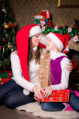 Mom and daughter with gifts near a Christmas tree. — Stock Photo