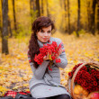 Girl with flowers and fruits in a basket in autumn forest — Stock Photo