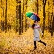 Girl in the forest running with umbrella — Stock Photo #34547783
