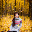 Woman sitting in a park in autumn — Stock Photo