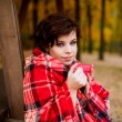 Girl in a red plaid drinking tea — Foto Stock