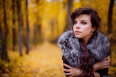 Girl with fur scarf in autumn forest — Stock Photo