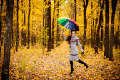 Girl in the forest running with umbrella — Stock Photo