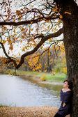 девочка сидит возле дерева в осенний парк — Стоковое фото