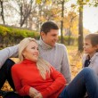 Family sitting in the autumn leaves in the park — Stock Photo