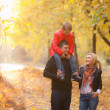 Family walking in the autumn park — Stock Photo
