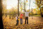 Family playing with autumn leaves in the park — Stock Photo