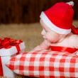 Little boy Christmas hat with a gift — Stock Photo