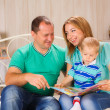 Family reading the book with son — Stock Photo