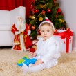 Boy playing with toy near Christmas tree — Stock Photo