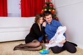 Family near the Christmas tree — Stock Photo