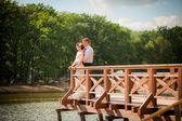 Wedding couple standing on the wooden pier — Stock Photo