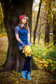Girl with autumn leaves near a tree — Stock Photo