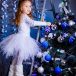 Foto Stock: Little girl decorating the Christmas tree.