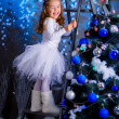 Stockfoto: Little girl decorating the Christmas tree.
