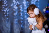 Girl in white warm gloves and headphones playing with snow — Stock Photo