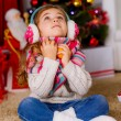 Stock Photo: Little girl with mandarins looking up near Christmas tree