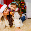 Girl with her mother lying together near Christmas tree — Stock Photo