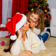 Girl with her mother lying together near Christmas tree — Stok fotoğraf