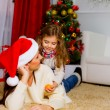 Girl with her mother lying together near Christmas tree — Photo
