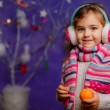 Stock Photo: Little girl with mandarins on Christmas background