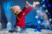 Girl in hat and mittens throws snow. — Stock Photo