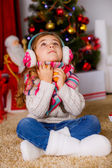 Little girl with mandarins looking up near the Christmas tree — Stock Photo