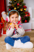 Happy little girl with mandarins near the Christmas tree — Stock Photo