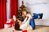 クリスマスの木の近くの彼女の娘と遊ぶ母 — ストック写真