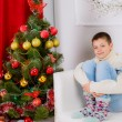 Stock Photo: Teenager boy near Christmas tree