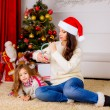 Stock Photo: Mother and daughter near Christmas tree