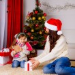 Stock Photo: Mother and daughter opening present near Christmas tree