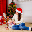 Mother and daughter near Christmas tree — Stock Photo #36658195