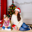 Stock Photo: Mother and daughter near Christmas tree with present