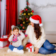 Mother and daughter near Christmas tree with present — Stock Photo
