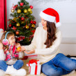Little girl with her mother near Christmas tree with oranges — Stock Photo #36658253