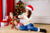 Mother and daughter near Christmas tree — Stock Photo
