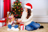 Little girl with her mother near Christmas tree with oranges — Stock Photo