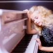 Blond girl sitting  near white piano — Photo