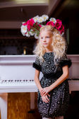 Little blond girl standing near white piano — Stock Photo