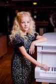 Blond girl standing near white piano — Stock Photo