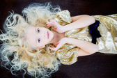 Little blond girl in golden dress — Stock Photo