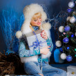 Girl with a gift in hands near the Christmas tree — Stockfoto