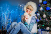 Girl sitting near Christmas tree — Stock Photo