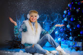 Girl in earmuffs sitting near Christmas tree — Stock Photo